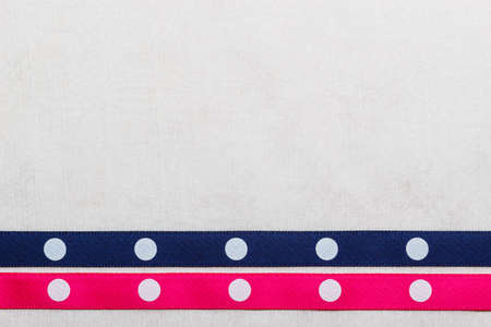 navy blue background: Festive celebration party frame. Polka dot navy blue and pink satin ribbon on white cloth background