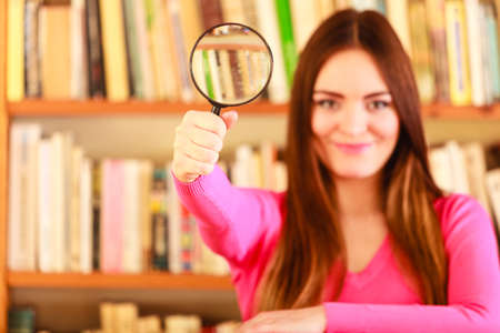 findings: Investigation exploration education concept. Closeup intelligent student girl in library, woman holding magnifying glass loupe