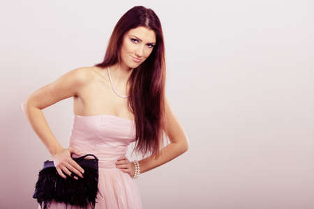 clutch bag: Beauty, fashion and elegant people concept - young brunette slim woman in bright strapless dress holds black clutch bag Stock Photo