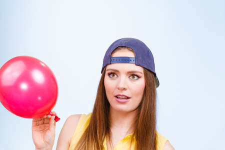 disgusted: Teenage girl making funny silly faces. Young trendy woman in jeans cap holding red balloon.