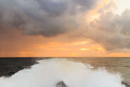 Beautiful seascape evening stormy sea horizon and kielwater seen from ship, trail on the water after the ferry sail, wake of boat.
