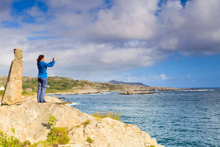 Tourism vacation and travel. Woman tourist taking photo with camera, enjoying ocean view from rocky coast, Norway Scandinavia. Stock Photo