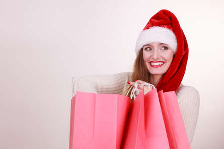 buying time: Christmas time. Young latin woman wearing santa claus hat holding red shopping bags buying presents gifts