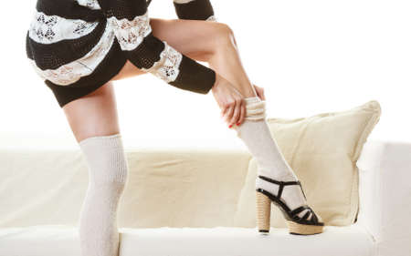 Fashionable woman legs. Girl in striped dress puts on woolen stockings indoor at home