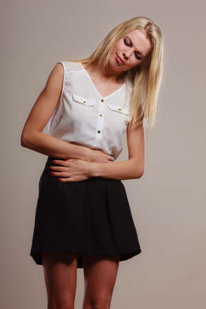 Bellyache, indigestion or menstruation. woman suffering from stomach pain studio shot on gray