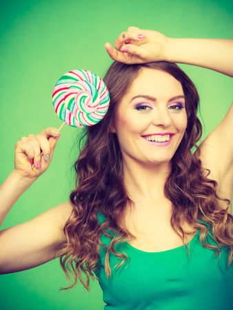 Woman beautiful cheerful girl holding colorful lollipop candy in hand. Sweet food and happiness concept. Studio shot vivid color green background, toned image Stock Photo