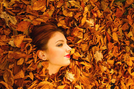 Ecology earth, eco friendly and love nature concept. Portrait young redhaired woman cover in autumn orange leaves.