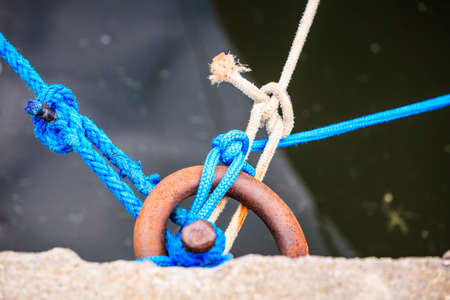 Dock ring trussed wrapped with mooring rope, docking line, hawser in harbor docks.