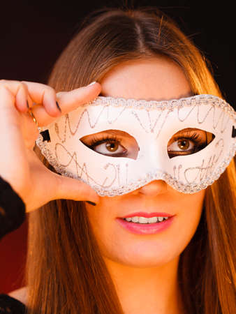 Party time, holidays, people and celebration concept. Woman long hair holds carnival white mask close up