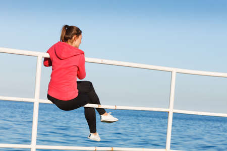 mujer mirando el horizonte: Woman resting after doing sports outdoors. Fitness girl in sportswear sitting on pier relaxing looking at horizon back view