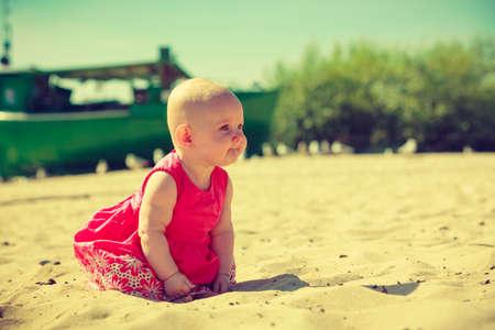 Niño pequeño sentado, jugando y divirtiéndose en la playa cerca del mar. Foto de archivo