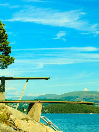 Las vacaciones de verano y el deporte peligroso. Vista de trampolín. Trampolín para bucear en el agua. Fiordo paisaje