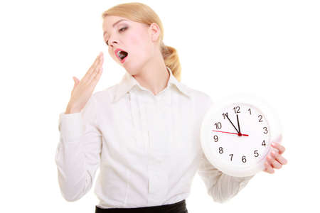 working hours: Portrait of overworked businesswoman showing clock. Sleepy blond girl yawning isolated on white. Time management and long working hours. Studio shot. Stock Photo