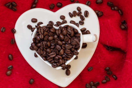 love pic: Coffee klatsch concept. Heart shaped white cup filled with roasted coffee beans on red cloth background Stock Photo