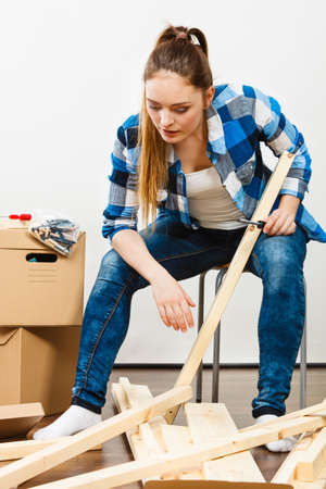 Woman moving into new apartment house assembling furniture with screwdriver. Stock Photo