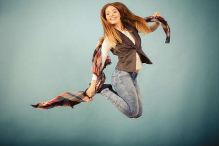 entertaiment: Movement fun and fashion concept. Attractive woman is jumping up. Beautiful girl with long hair wearing jeans and scarf.