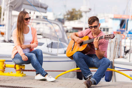 Love romance affection music sound talent concept. Girl charmed by musican. Young guitarist playing on instrument in port.