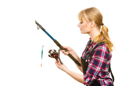 dungarees: Fishing concept. Attractive woman in dungarees, pink check shirt holding and looking at rod. Isolated background Stock Photo