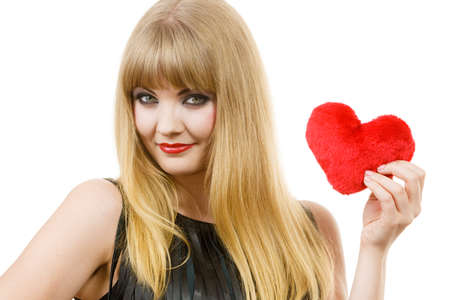 feminity: People in love, happiness. Young lady with red heart. Beautiful blonde woman holding ticker. Attractive girl has make up and black outfit.