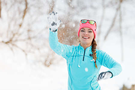 palle di neve: Girl playing games in snow. Young woman tossing snowballs. Health nature fashion fitness concept.