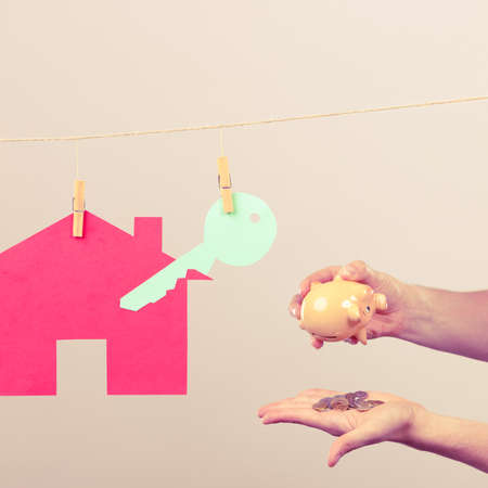 piggybank: Red house with green key hang on laundry line and male hands with piggybank coins. Selling and buying home concept. Stock Photo