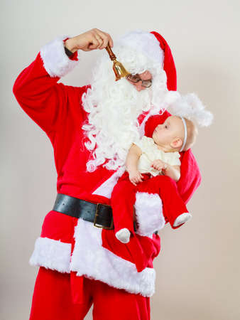 Christmas family holiday concept. Father wearing santa claus hat holding baby in aureole and showing bell.