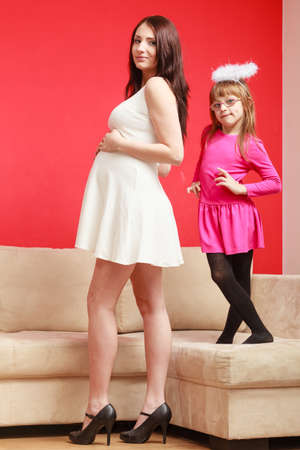 Parenthood, family love, relationship concept. Pregnant woman wearing short white dress and high heels standing next to her daughter dressed as little angel in aureole.