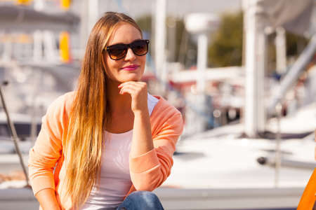 Fashion leisure relax concept. Attractive girl sitting on pier. Young lady enjoying sunny day on coast.