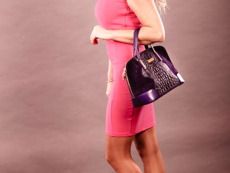 Fashion of women. Clothing and accessories. Mid aged blonde fashionable woman with handbag. Elegant lady in pink dress with black bag.