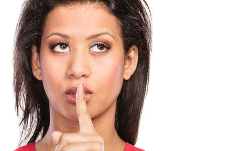 Young mixed race woman girl with finger on lips showing hand quiet silence sign gesture isolated on white.