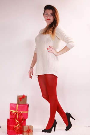 Woman in high heels shoes red pantyhose with many presents gift boxes. Christmas season celebration concept.