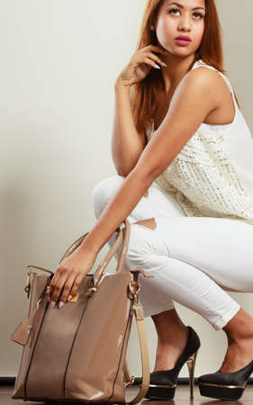 mulatto woman: Fashion concept. Clothing and accessories. Mulatto woman holding beige handbag. Lady in white clothing high heels with lacquered leather bag.