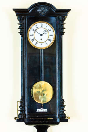 reloj de pendulo: viejo reloj de péndulo de madera grande que cuelga en la pared Foto de archivo