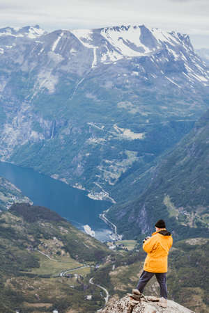 valley view: Tourism vacation and travel. Male tourist taking photo with camera, enjoying Geiranger fjord and mountains landscape from Dalsnibba Plateau viewpoint, Norway Scandinavia. Stock Photo