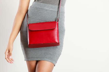 shapely: Female fashion. Closeup girl shapely figure wearing gray skirt with red leather bag handbag. Studio shot