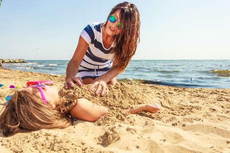 Spiel und Spaß im Sommer. Entzückende Mädchen Tochter mit ihrer Mama, die Spaß haben. Familie verbringen Zeit zusammen am Strand am Meer.