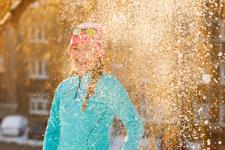 having fun in winter time: Girl having fun time with snow. Young woman playing in winter park. Health nature relax fashion fitness concept. Stock Photo