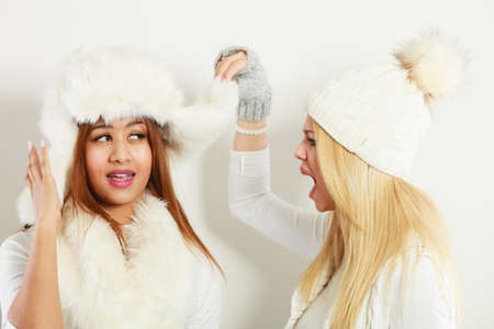 Relationship gossip. Two multiethnic women in winter clothing whispering secret, funny face expression, studio shot