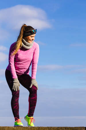 Woman athlete girl training wearing warm sporty clothes outside by seaside in cold weather. Sports and activities in winter or autumn time. Stock Photo