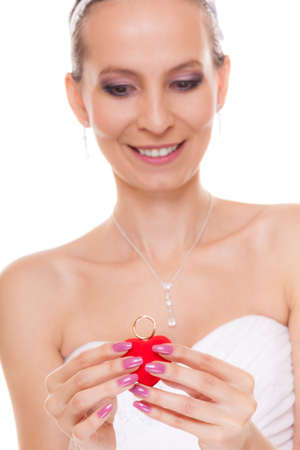 Excited happy bride holding showing engagement ring box. Surprised woman in white wedding dress isolated on white background.