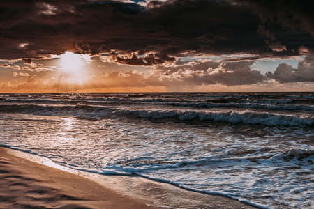 Amazing colorful sunset over evening sea horizon, clouds sky and sandy beach. Tranquil scene. Natural background. Landscape.
