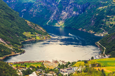 fantastic view: Tourism vacation and traveling. Fantastic view on Geirangerfjord green mountains landscape and village Geiranger, travel destination in Norway Scandinavia.