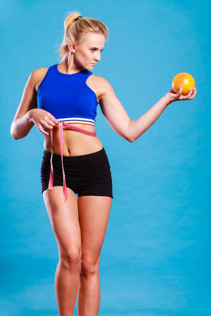 losing control: Time for diet slimming weight loss. Health care and healthy nutrition. Young fitness woman fit girl with measure tape and grapefruit on blue