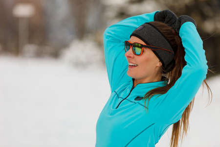 Winter holidays, sporty people concept. Lady spending free time in park. Sporty girl wearing sunglasses enjoying good wintry weather.