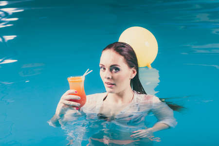 Happy woman with balloons and cocktail drink alcohol in swimming pool water. Pretty attractive girl relaxing.