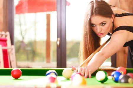 concept de la concurrence. Jeune fille ciblée amuser avec billard. Jolie mode de passer du temps de la femme sur le jeu rivalité.