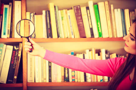 lupa: Exploration education concept. intelligent beauty hipster student girl in library, woman holding magnifying glass loupe.