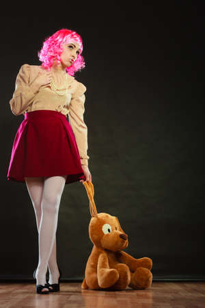 Mental disorder concept. Young childlike woman wearing like puppet doll and big dog toy standing dark black background