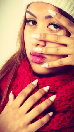 mulatto woman: Closeup of young mulatto woman showing white painted nails. Mixed race girl in wintertime clothes, studio shot