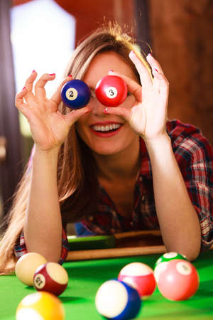 entertaiment: Play jokes and fun concept. Young happy girl having fun with billiard. Fashionable woman playing spending time on entertaiment.